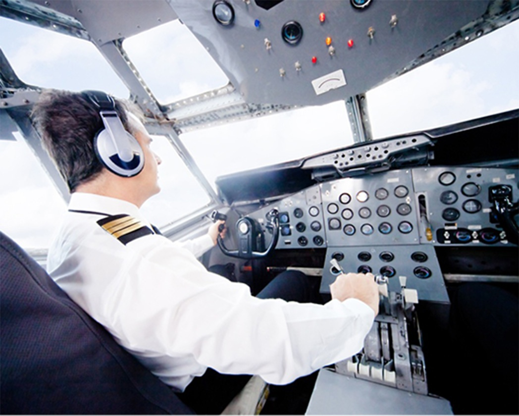 Pilot in an airplane cabin flying a plane@2x